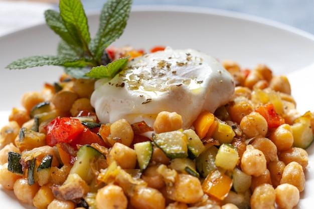 Soffriggere vegetariano piccante fatto in casa con ceci e dadi di pepe e zucchine con un uovo fritto e qualche decorazione di menta in un piatto bianco. avvicinamento.