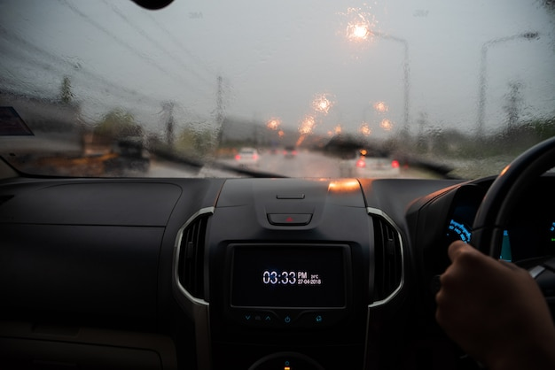 Soft focus di forti piogge sul parabrezza di sera
