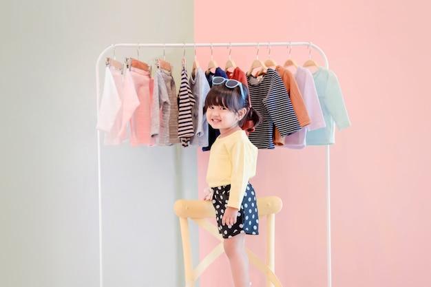 Soft focus di un bambino di due anni in piedi davanti al rack di stoffa