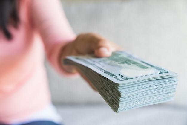 Soft focus sulle mani di donna che propongono denaro noi banconote da un dollaro a voi.