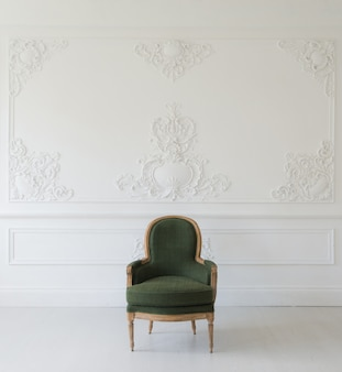 Soggiorno con elegante poltrona verde antico su elementi di design roccoco modanature in stucco a bassorilievo di design bianco a parete di lusso