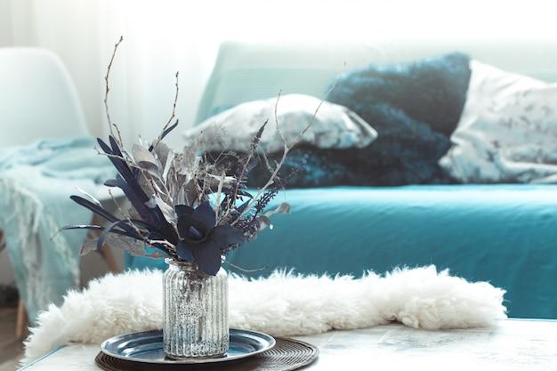 Soggiorno moderno, con fiori artificiali in un vaso e oggetti di arredamento per la casa sul tavolo luminoso in legno.
