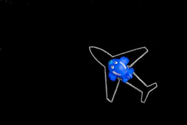 Sogna in grande. piccolo aeroplano blu del giocattolo sulla siluetta dell'aereo di linea dissipato gesso
