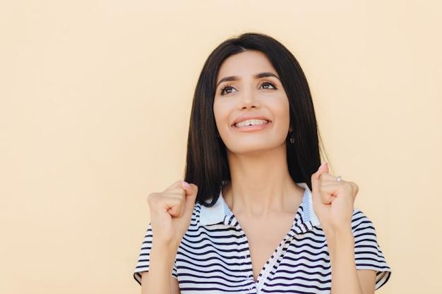 Sognante donna positiva con i capelli lisci neri, tiene le mani nei pugni