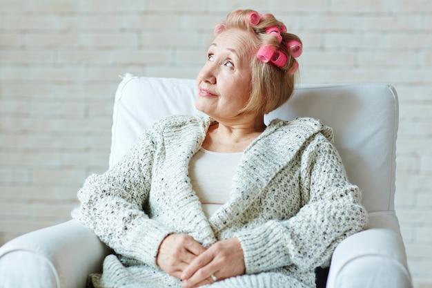 Sognante donna senior sulla poltrona