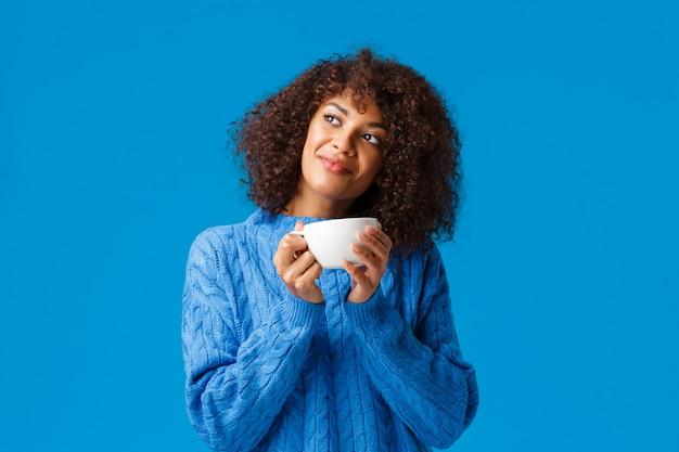 Sognante, romantica e sensuale bella donna afro-americana, in maglione, testa inclinata e distanza di osservazione, contemplare fuori dalla finestra uno splendido scenario innevato, bere tè caldo, tenendo la tazza