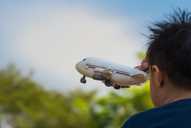 Sogno del ragazzo con l'aeroplano del giocattolo che sorvola il cielo, concetto di pensiero del bambino creativo.