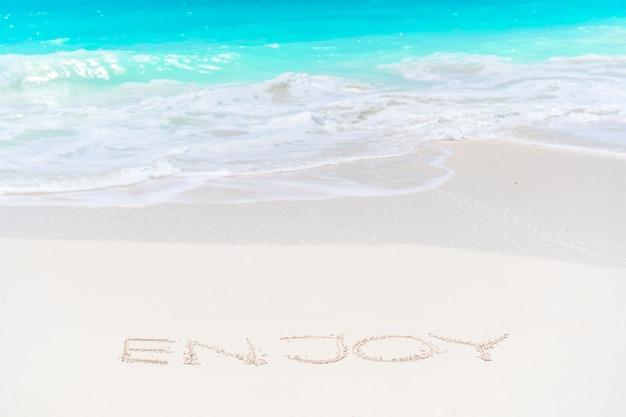 Sogno scritto sulla spiaggia di sabbia con morbida onda dell'oceano