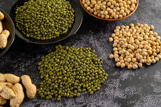 Soia, arachidi e fagiolo verde su un pavimento di cemento nero.
