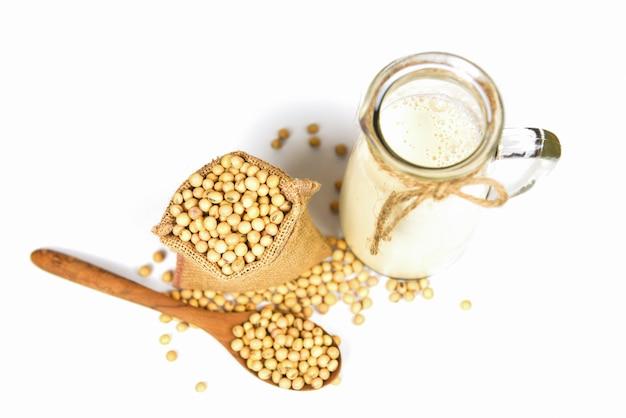 Soia sul cucchiaio di legno e fagioli di soia secchi nel sacco su bianco