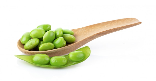 Soia verde in cucchiaio di legno sulla parete bianca