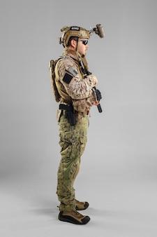Soldato delle forze speciali con il fucile su bianco.
