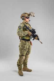 Soldato delle forze speciali con il fucile su fondo bianco.