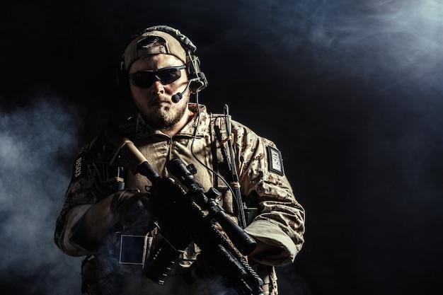 Soldato delle forze speciali con il fucile su fondo scuro