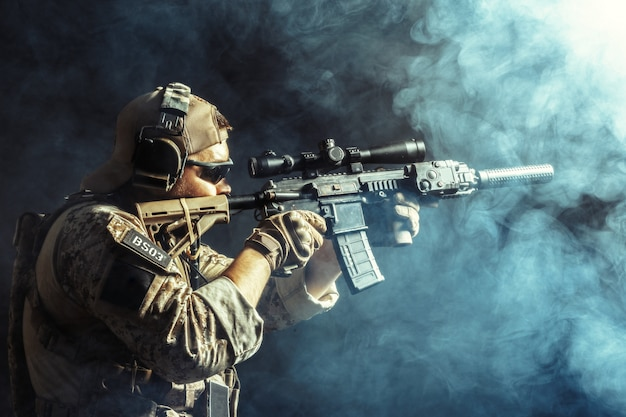 Soldato delle forze speciali con il fucile su oscurità