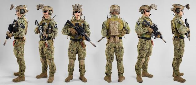 Soldato delle forze speciali con il fucile su superficie bianca.