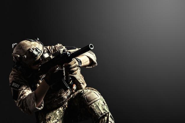 Soldato delle forze speciali con il fucile su superficie scura