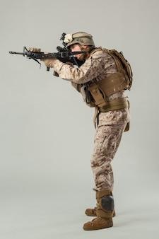 Soldato in mimetica che tiene il fucile
