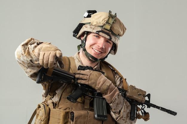 Soldato in mimetica tenendo il fucile