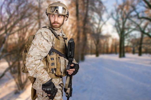 Soldato moderno con il fucile in una foresta
