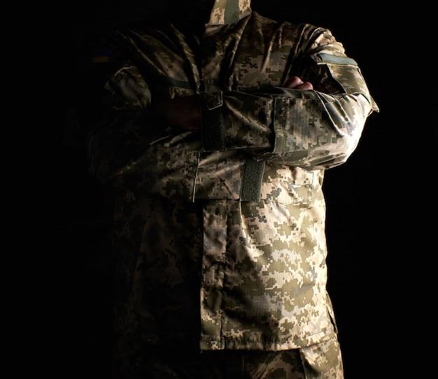 Soldato ucraino in uniforme mimetica si erge con le braccia incrociate sul petto