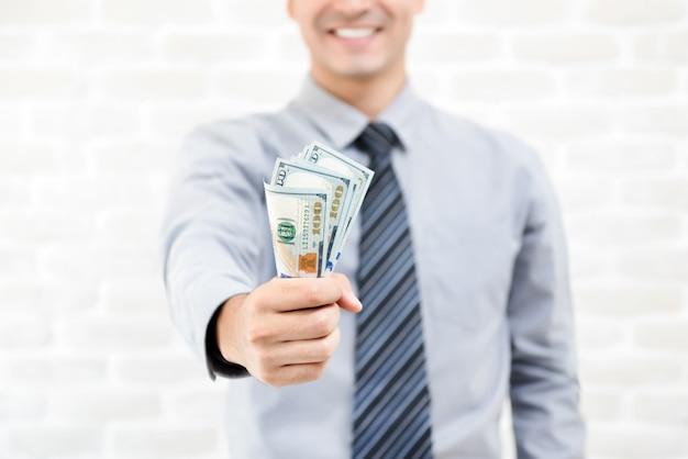 Soldi, banconote del dollaro degli stati uniti, in mano dell'uomo d'affari
