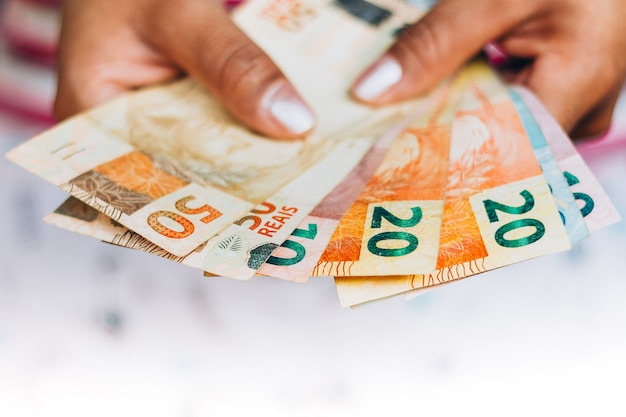 Soldi brasiliani - note reali - valuta brasiliana - concetto di finanza - investimenti - ricchezza - soldi della tenuta della donna.