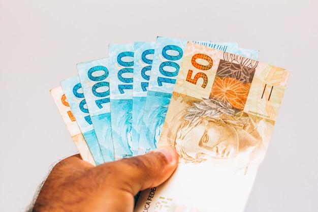 Soldi dal brasile. note reali, soldi brasiliani nella mano di un uomo di colore. note di 100 e 50 reais. concetto di inflazione, economia e affari. sfondo chiaro