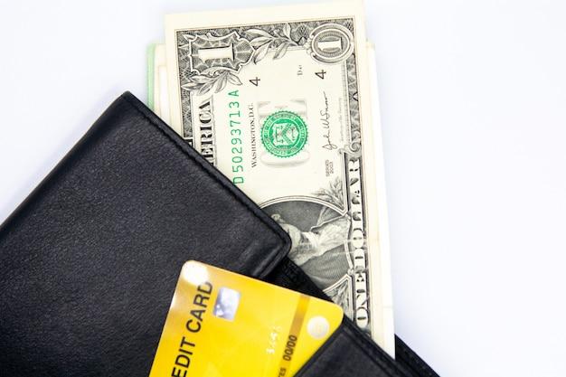 Soldi del dollaro in portafoglio nero con la carta di credito sulla tavola bianca