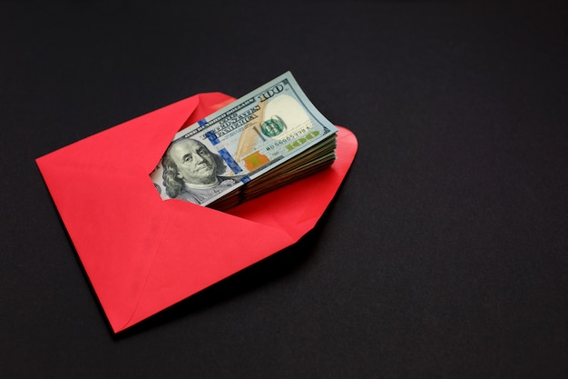 Soldi del dollaro nella busta rossa sul nero