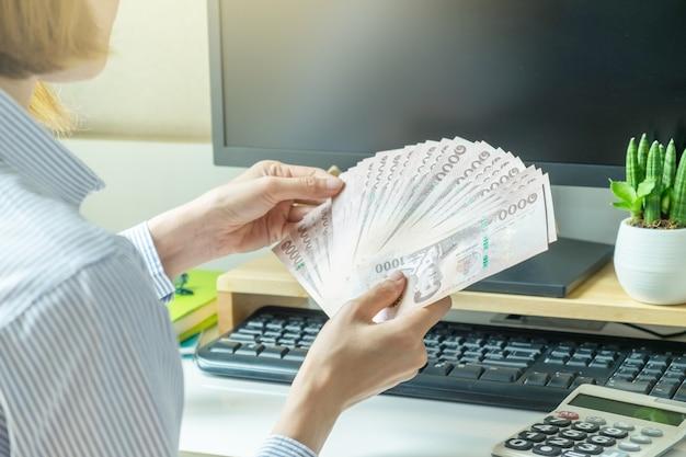 Soldi della banca nota della tailandia tengono dalla mano della donna sulla scrivania