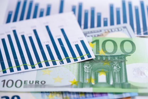 Soldi delle banconote dell'euro e del dollaro americano sul documento del foglio elettronico del grafico di carta.