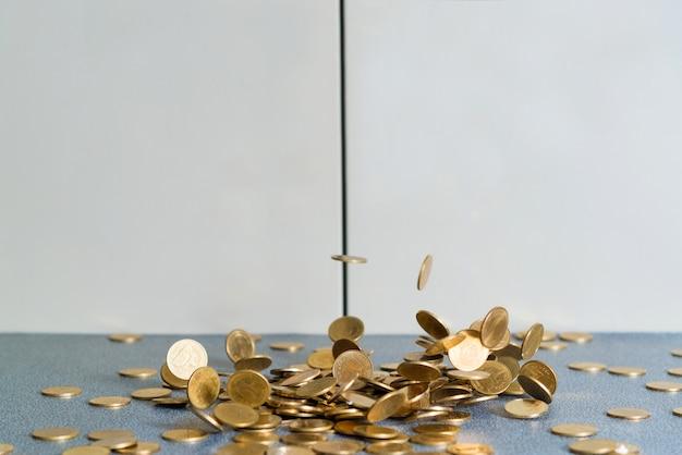Soldi delle monete d'oro che cadono sul tavolo dell'ufficio