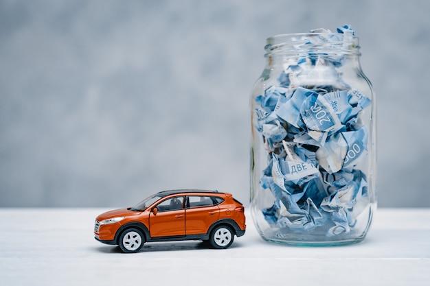 Soldi di carta sgualciti in un barattolo di vetro. concetto di risparmiare denaro per un'auto