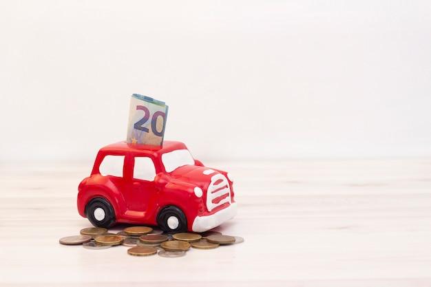 Soldi e monete sotto un salvadanaio sotto forma di un'auto