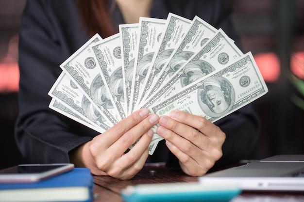 Soldi in mano, donna con dollari americani, banconote degli stati uniti.