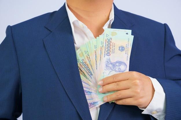 Soldi in vietnam tenere a portata di mano uomo d'affari che indossa un abito blu