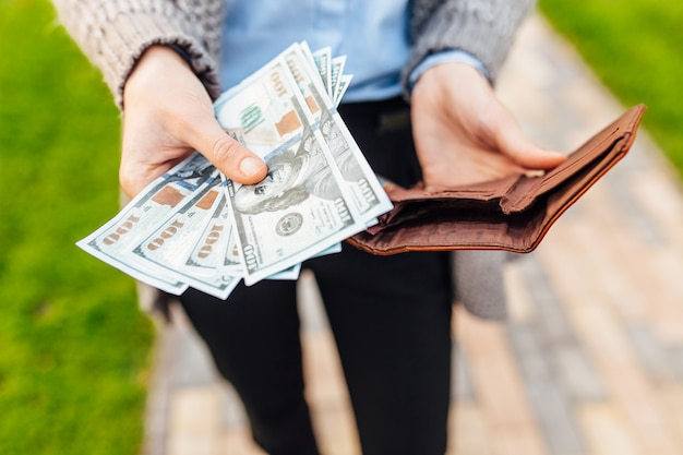 Soldi nel tuo portafoglio. la persona estrae denaro dal suo portafoglio e dà soldi a qualcuno. concetto di business, guadagni, stipendio