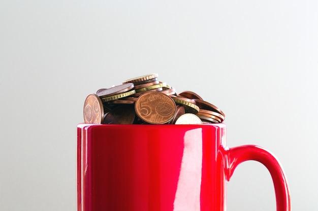 Soldi risparmiati in una tazza rossa variopinta per finanziare gli obiettivi che traboccano di euro monete, concetto di affari