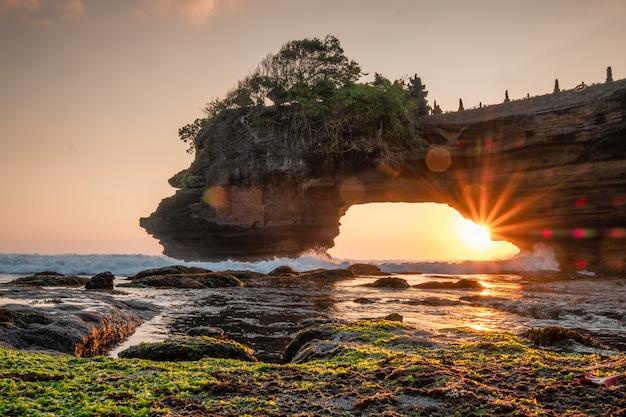 Sole attraverso della scogliera rocciosa sulla spiaggia al tramonto