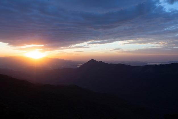 Sole che sorge sopra le nuvole, sulle colline