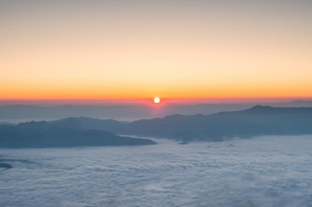 Sole che splende sopra l'orizzonte con la montagna