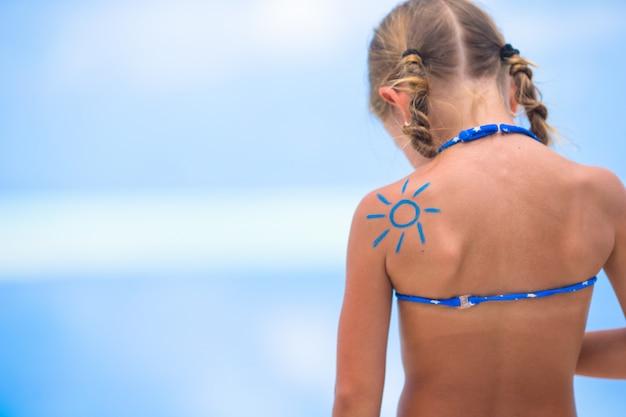 Sole dipinto da crema solare sulla spalla del bambino