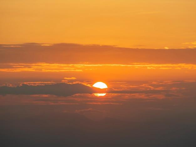 Sole luminoso e cielo drammatico arancio di alba