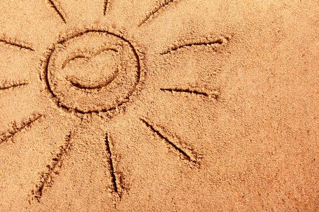 Sole sorridente disegnato su una spiaggia di sabbia