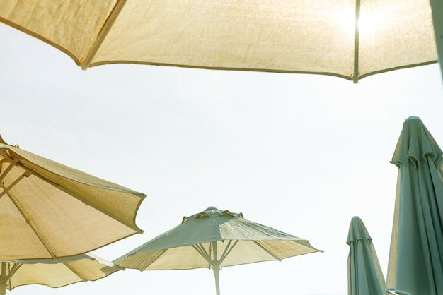 Sole splendere, cielo e ombrelloni sullo sfondo.