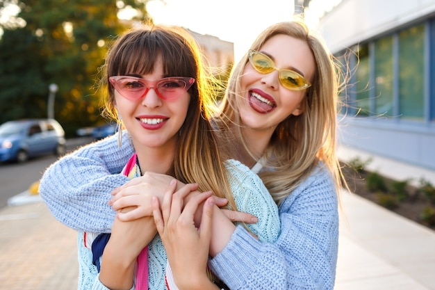 Soleggiato ritratto positivo di felice coppia lesbica che gode del tempo insieme, colori solari, abiti color pastello alla moda e occhiali da sole, primavera autunno tempo, buone vacanze in europa.