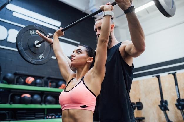 Sollevamento di potenza della giovane donna aiutato dal suo personal trainer