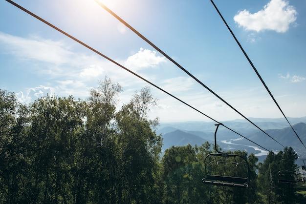 Sollevare in montagna in giornata di sole. valle della montagna con funivia, vista dall'alto. vegetazione verde nelle montagne altai.