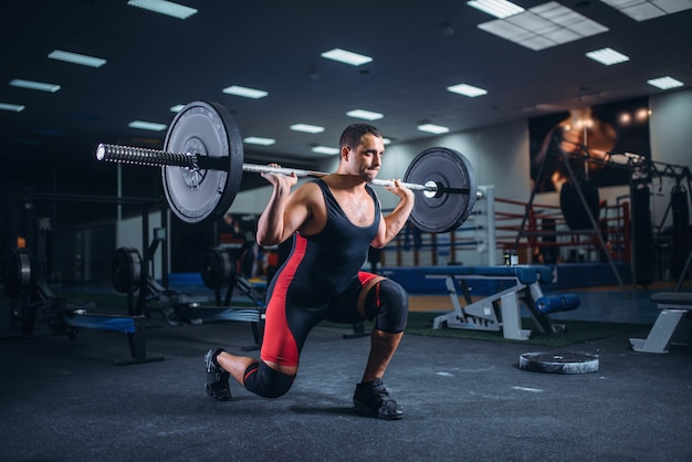 Sollevatore di pesi che fa squat con un bilanciere in palestra
